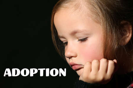 Adoption concept. Sad little girl on black background