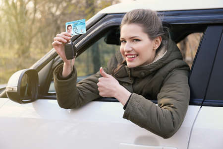 Woman with driving license and key in car