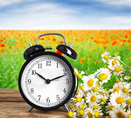 Alarm clock with flowers on wooden table against landscape background.