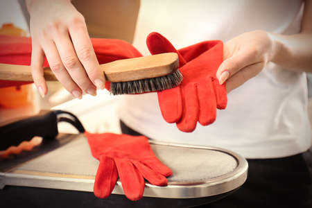 Dry cleaning business concept. Woman working with glove and brush Stock Photo