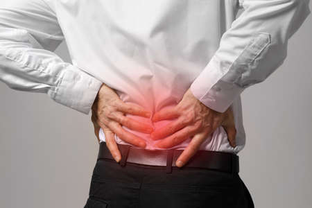 Man suffering from back ache on gray background. Health care concept