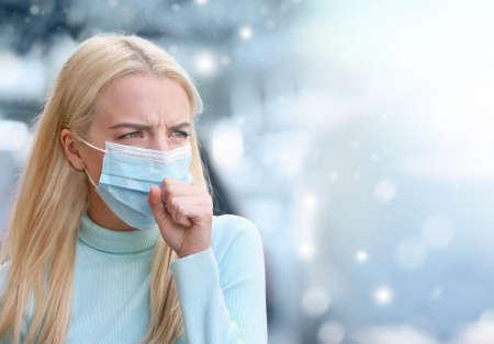 Sick woman wearing facial mask in winter, outdoor
