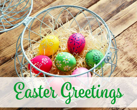 Greeting card design. Basket with colourful Easter eggs on wooden background