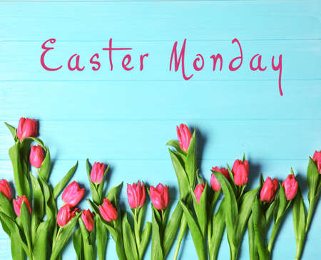 Text EASTER MONDAY and beautiful tulips on blue wooden background