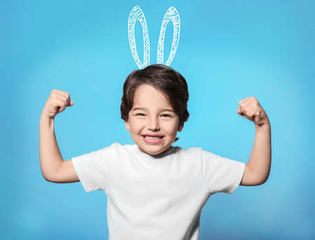 Cute little boy with drawn bunny ears on color background 免版税图像