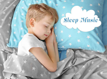 Concept of music for sleep and meditation. Cute little boy sleeping in bed at home
