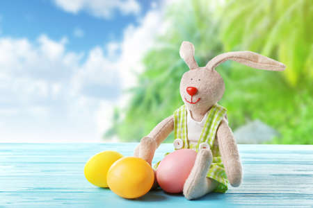 Easter eggs with bunny toy on wooden table against landscape background Stock Photo