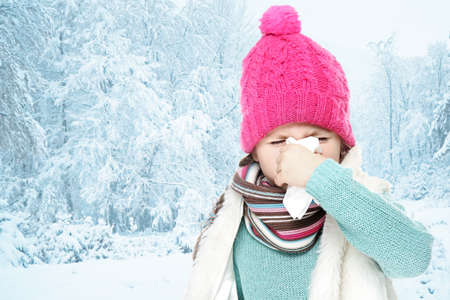 Little girl with tissue in winter, outdoor
