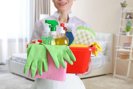 Chambermaid with cleaning equipment on bedroom background Stock Photo