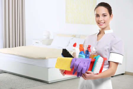 Chambermaid with cleaning equipment on bedroom background