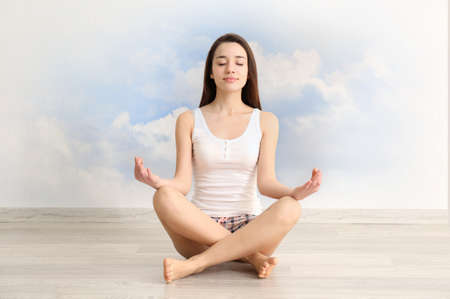 Young woman meditating in lotus pose on sky background. Concept of meditation for sleep Stock Photo