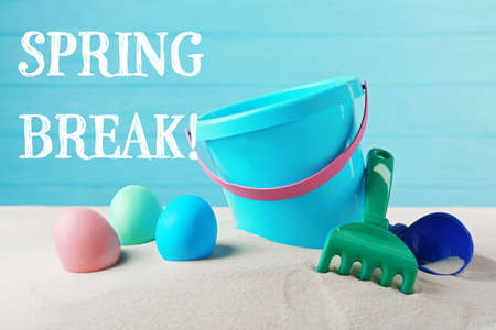 Spring break concept. Colorful Easter eggs and toddler beach kit on sand Stock Photo