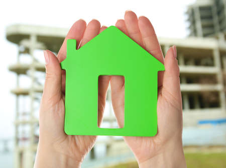 Energy savings concept. Female hands holding house shaped figure on construction site background Standard-Bild