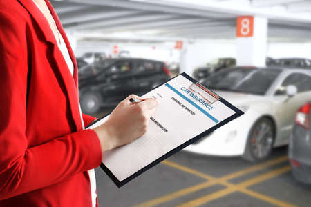 Woman filling in car insurance form on auto center background