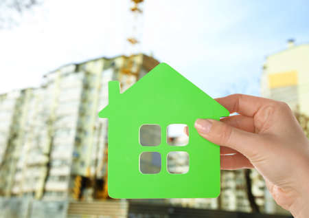 Energy savings concept. Female hand holding house shaped figure on construction site background