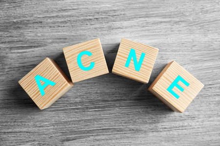 Word ACNE of cubes on wooden background. Skin care concept