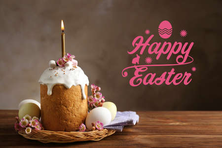 Wicker plate with sweet cake and eggs on wooden table. Text HAPPY EASTER on background