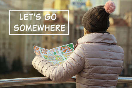 Woman holding map on street. Text LETS GO SOMEWHERE on background Stock Photo