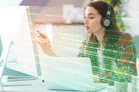 Concepto de desarrollo del programa. Mujer joven escuchando música mientras trabaja con la computadora% 00 Foto de archivo