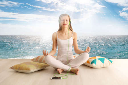 Young woman meditating in lotus pose on seascape background. Concept of music for sleep
