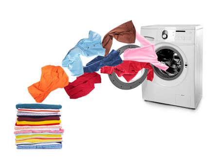 Lavatrice e vestiti volanti su sfondo bianco