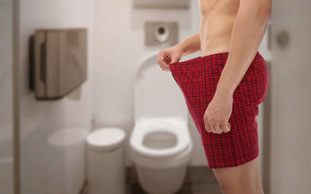 Young man in underwear on toilet background. Urology concept