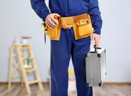 Electrician with tools on blurred background