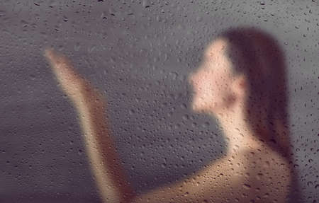 View through steamy glass on young woman in shower