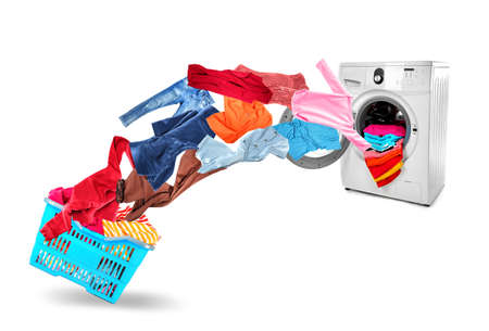 Washing machine and flying clothes on white background Фото со стока