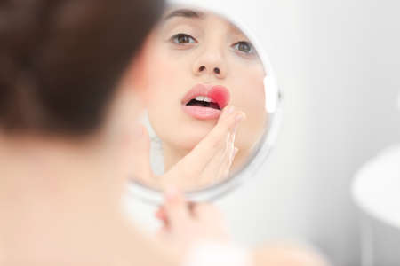 Young woman looking in mirror. Herpes virus concept