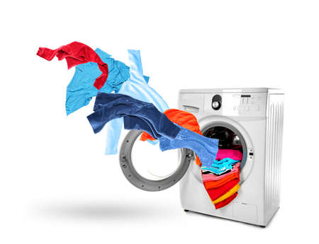 Washing machine and flying clothes on white background Stock Photo