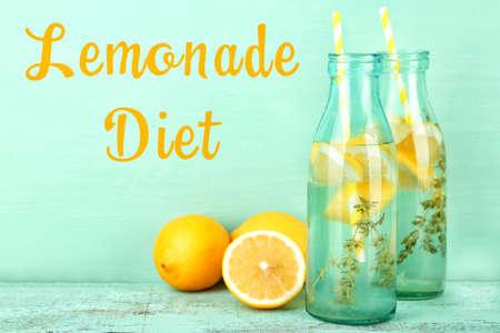 Lemonade diet concept. Bottles with tasty drink on wooden table