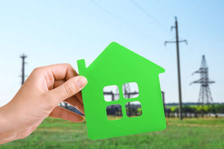Energy savings concept. Female hand holding house shaped figure on high voltage towers background