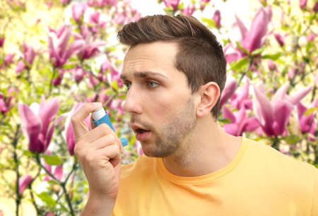 Young man using asthma inhaler outdoor