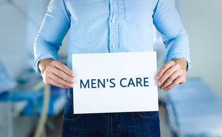 Man holding paper with text MENS CARE, closeup. Health care concept. Stock Photo