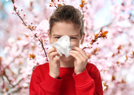 Seasonal allergy. Little boy with tissue outdoor