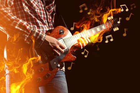 Jeune homme jouant de la guitare électrique et le feu doit instrument sur fond sombre Banque d'images - 91470186