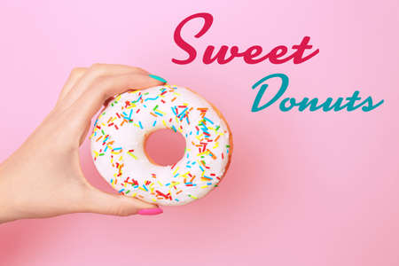 Woman holding tasty donut on color background Stock Photo