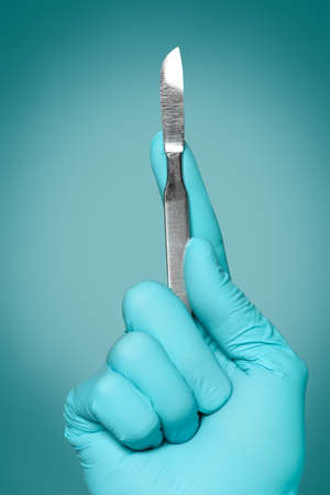 Surgeon holding lancet on color background