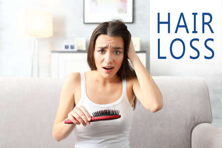 Hair loss concept. Young woman with brush at home Standard-Bild