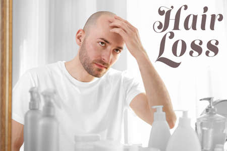 Hair loss concept. Man looking at mirror