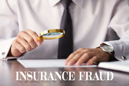 Insurance fraud concept. Man inspecting document with magnifier