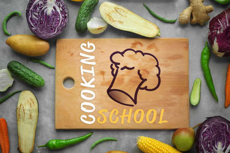 Cooking school concept. Wooden cutting board and fresh vegetables on gray background Banque d'images