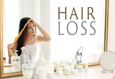 Concepto de pérdida de cabello. Mujer joven con cinta métrica delante del espejo% 00 Foto de archivo