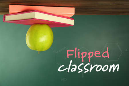 Flipped classroom concept. Inversed books and apple on blackboard background Banco de Imagens - 91278496