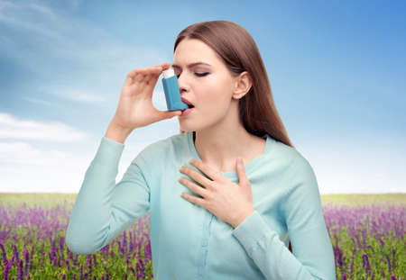Young woman using asthma inhaler outdoor Stock Photo