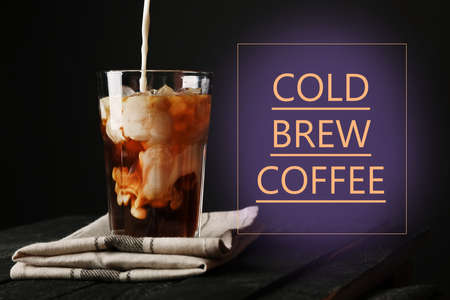 Pouring milk into glass with cold brewed coffee on black background