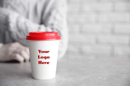 Paper cup with space for logo and woman on background