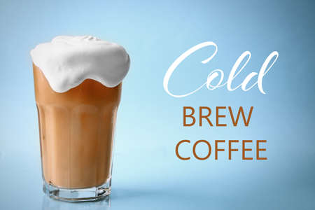 Glass of cold brewed coffee with cream on color background