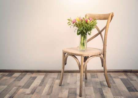 Chair and vase with bouquet of beautiful tulips on white wall background